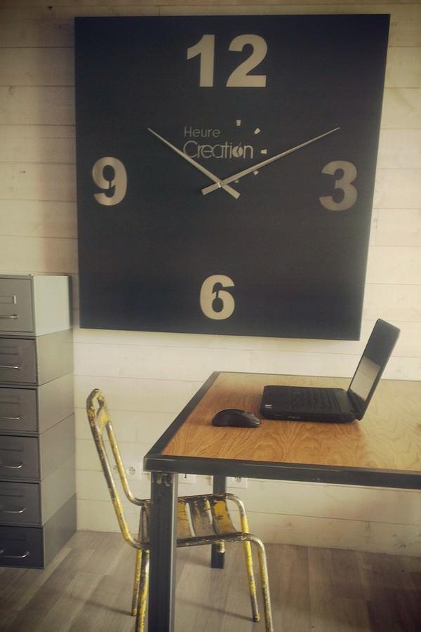 une grande horloge géante de forme carré en acier